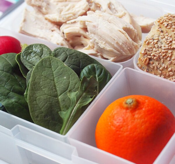 Portion Perfect helps you with your weight loss goals, here it's super easy with spinach and arugula leaves radishes, a whole wheat bun with seeds and multigrain, roasted organic chicken breast and a minneola tangerine orange in a portion perfect bento from bentology