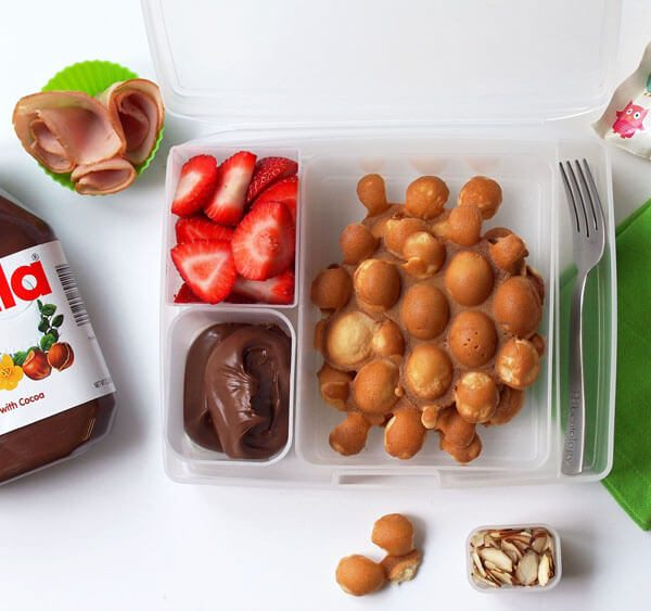 egg or bubble waffle maker with nutella, ham, and strawberries or any fruit and make their day, cool pack, napkin, lunchbag, and cutlery are all bentology