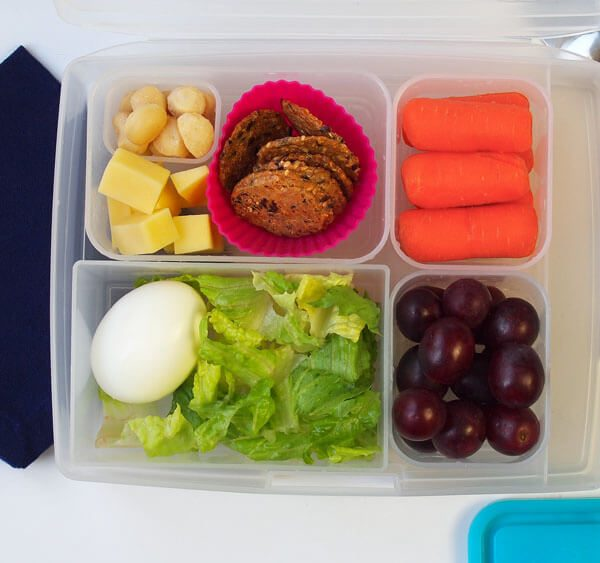 Easy School Lunch Gluten Free with egg, vegan crackers, carrots, grapes, cheese and macadamia nuts, bento box set with cutlery, napkin, yummy