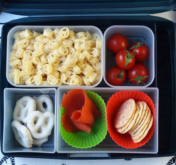 Bento Box lunch with Annie's Peace Pasta Lunch with parmesan cheese, alfredo sauce for kids, yummy keep the peace, with salmon, lemon, crackers with rice, tomatoes, yogurt pretzels