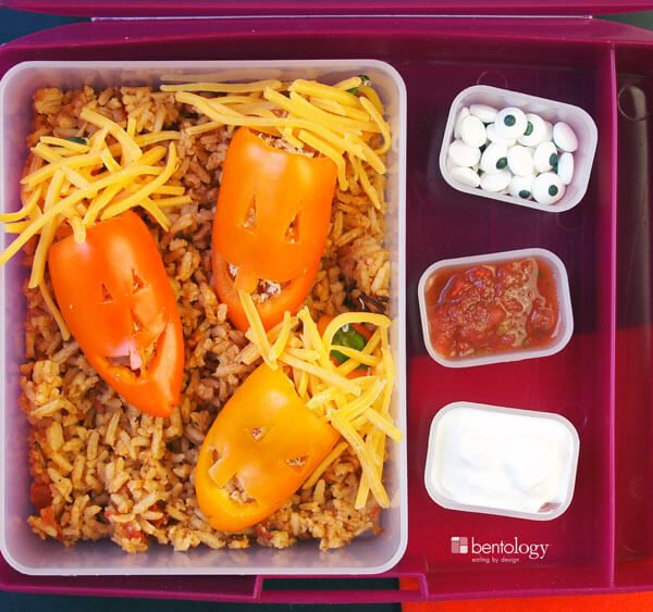 Halloween Themed Bento Box Lunch, jack o lantern Pumpkin Peppers with Rice, Chicken and Beans_raspberry_fork and spoon_Three Jacks with sour cream, salsa and little candy eyeballs