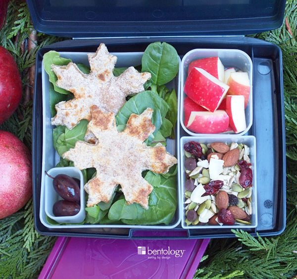 Holiday bento with grilled tortilla and cheese, olives, apples, salad, and trail mix with coconut, almonds, cranberries and dark chocolate chips