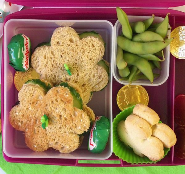 Veggie Lucky Kids' bento box lunch with cucumber sandwiches, edamame, mozzarella, and shamrock shortbread with lucky gold chocolate coins_blog